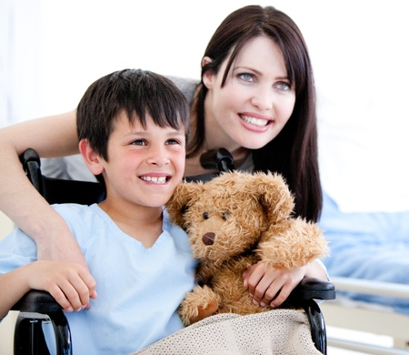 Smiling little boy in a wheelchair with his mother  photo