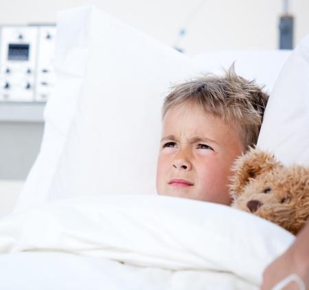 Sick little boy lying in a hospital bed  photo