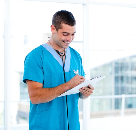 Concentrated male doctor making notes in a patient's folder  Stock Photo - 10106304