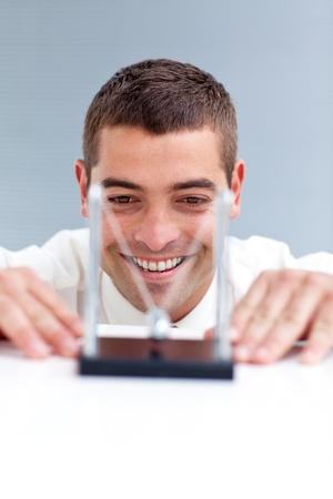 swaying: Businessman looking at kinetic balls Stock Photo