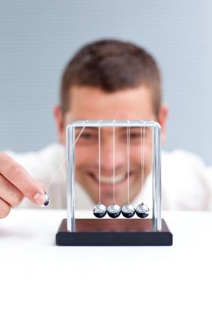 Businessman moving Newton balls photo
