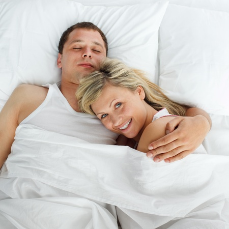 Woman lying in bed with a boy smiling at the camera photo