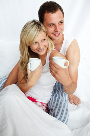 Couple in bed drinking coffee photo