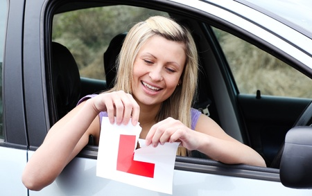 school exam: Happy young female driver tearing up her L sign