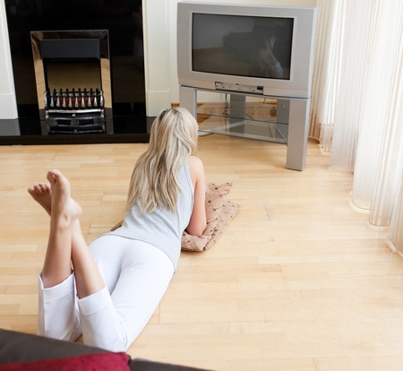 Blond woman watching TV lying on the floor photo