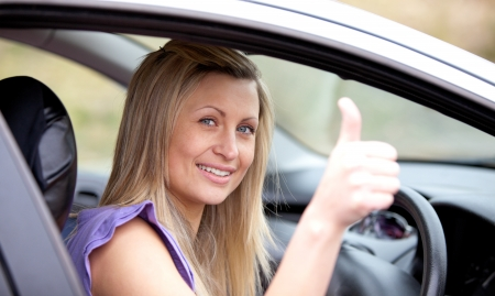 Smiling female driver with thumb up  photo