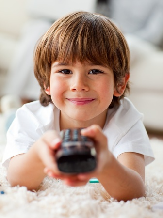Smiling little boy watching TV lying on the floor photo