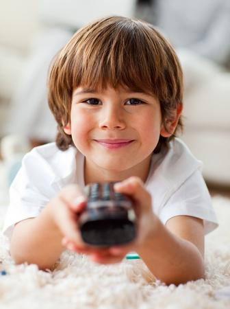 personas viendo television: Sonriendo little boy ver la tele acostado en el piso Foto de archivo
