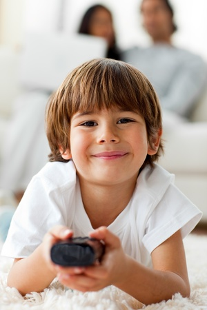 Adorable little boy watching TV lying on the floor  photo