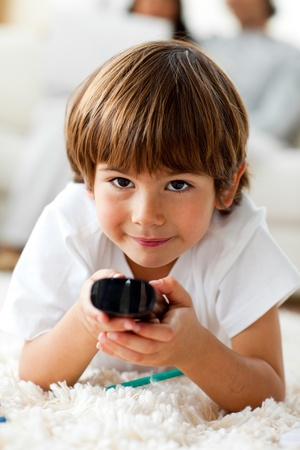 Smiling little boy holding a remote lying on the floor Stock fotó