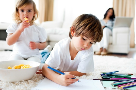 gir: Cute little gir eating chips and her brother drawing  Stock Photo