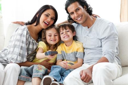 Gl�ckliche Familie vor dem Fernseher sitzen zusammen