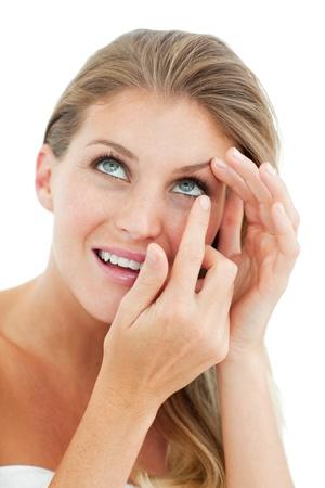 Attraktiv blond Frau setzen eine Kontaktlinse