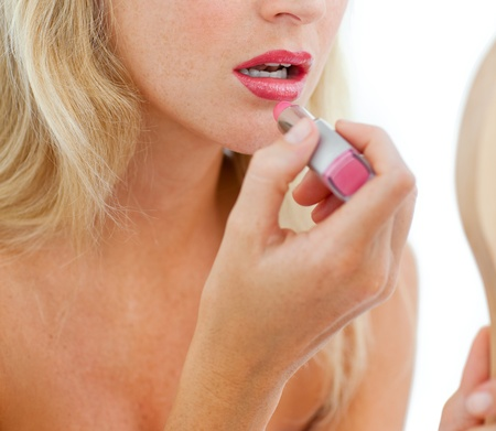 Close-up of a woman applying lipstick photo