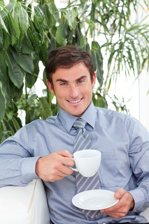 Businessman drinking a cup of coffee on sofa photo