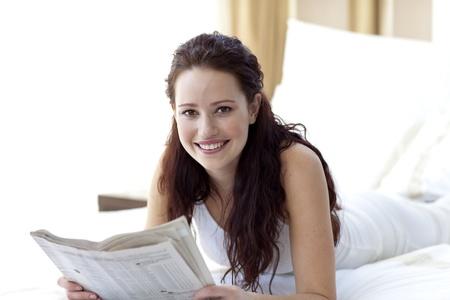 periodicos: Mujer Morena en la cama leyendo un peri�dico y sonriente Foto de archivo