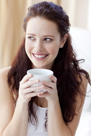 Beautiful woman drinking a cup of coffee in bed photo