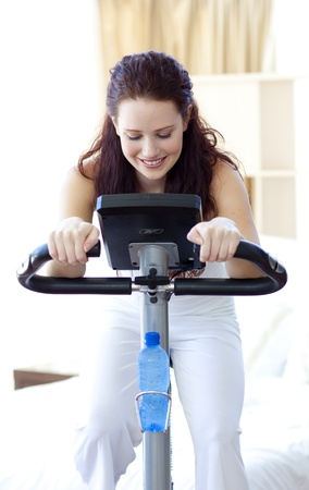 static bike: Beautiful woman doing spinning at home
