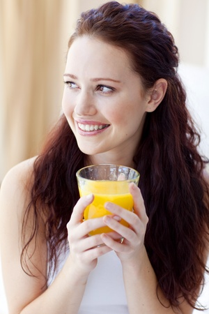 Portrait of woman drinking orange juice in bedroom photo