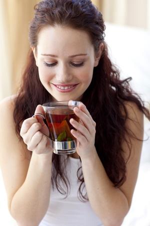 despertarse: Hermosa mujer beber una taza de t� en dormitorio Foto de archivo