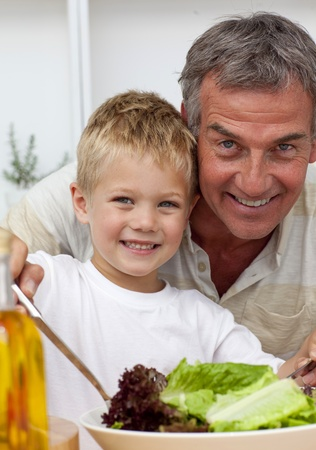 Happy grandfather cooking a salad with grandson photo
