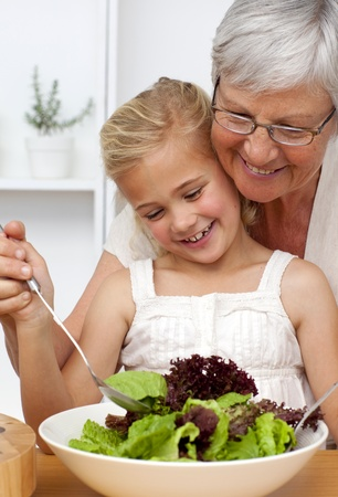 Happy grandmother cooking a salad with granddaughter photo