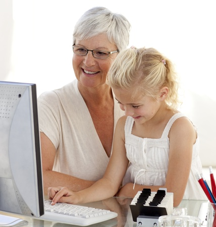 Granddaughter using a computer with her grandmother photo