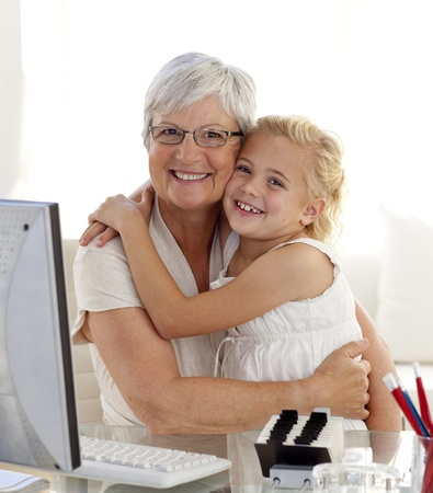 Granddaughter and grandmother hugging and using a computer photo