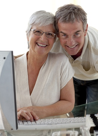 Happy senior couple using a computer photo