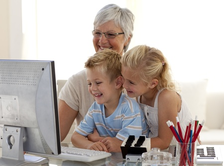 Children using a computer with their grandmother photo