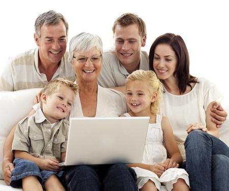 Gl�ckliche Familie mit einem Laptop im Wohnzimmer Lizenzfreie Bilder