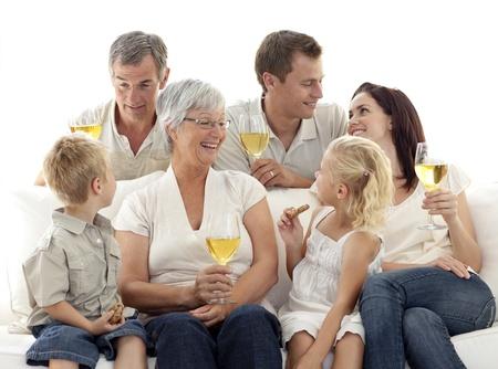 Familie in Wohnzimmer Wein zu trinken und Essen Kekse