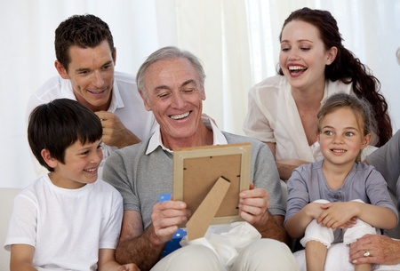 Grandfather looking at a photo with his family photo