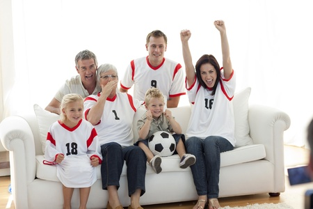 Happy family watching a football match in television photo