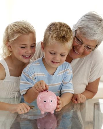 Close-up of grandmother and children saving money photo