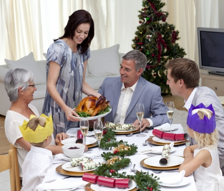Happy family celebrating Christmas dinner with turkey photo