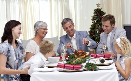 Family eating turkey in Christmas Eve photo