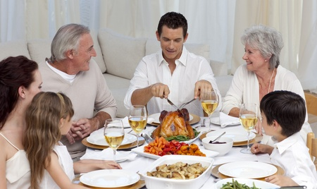 Father serving turkey to his family in a dinner photo