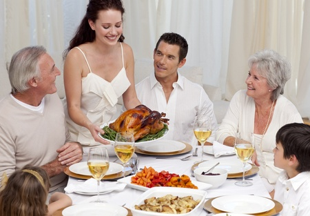 Woman showing turkey to her family for Christmas dinner photo