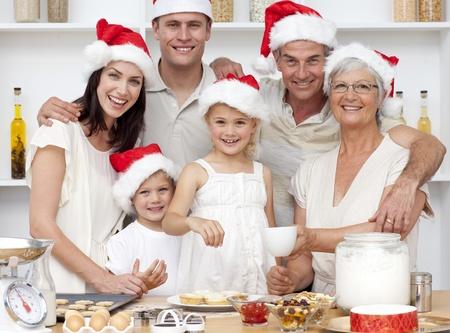 fiesta familiar: Ni�os hornear pasteles en la cocina con su familia de Navidad