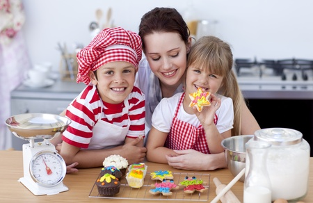 Smiling mother and children baking in the kitchen photo