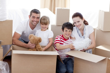 family moving house: Family moving home with boxes around Stock Photo
