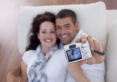 Couple playing with digital camera photo