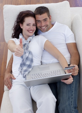 Couple buying online at home with thums up photo