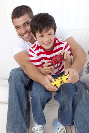 Smiling father and kid playing video games at home photo