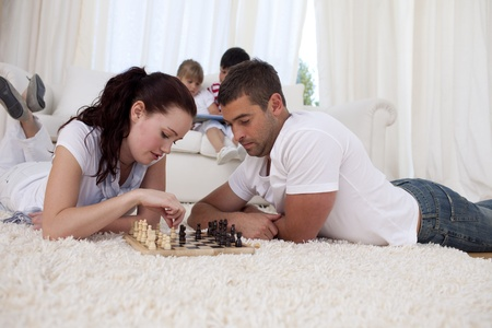 Couple playing chess on floor in living-room photo