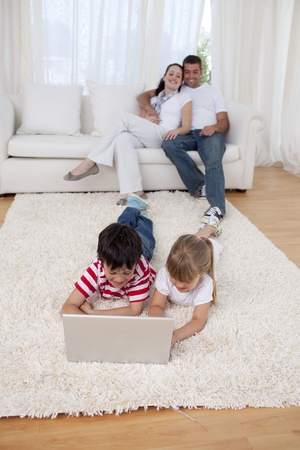 Brother and sister using a laptop on floor in living-room Stock Photo - 10112488