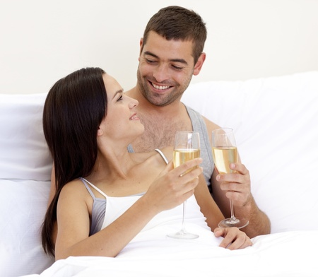Couple drinking champagne in bed photo