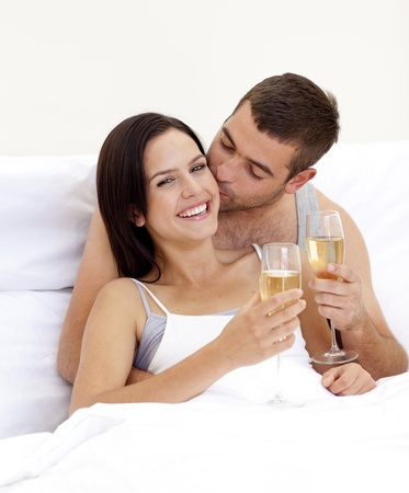 sexy woman on bed: Couple drinking champagne in bed in valentines day