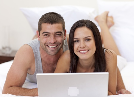 Smiling couple in bed using a laptop Stock Photo - 10111525